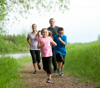 A family of four out for a jog on a nice day.